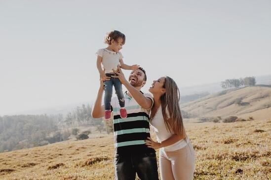 Por que contratar um seguro de vida - casal sorridente junto à filha pequena